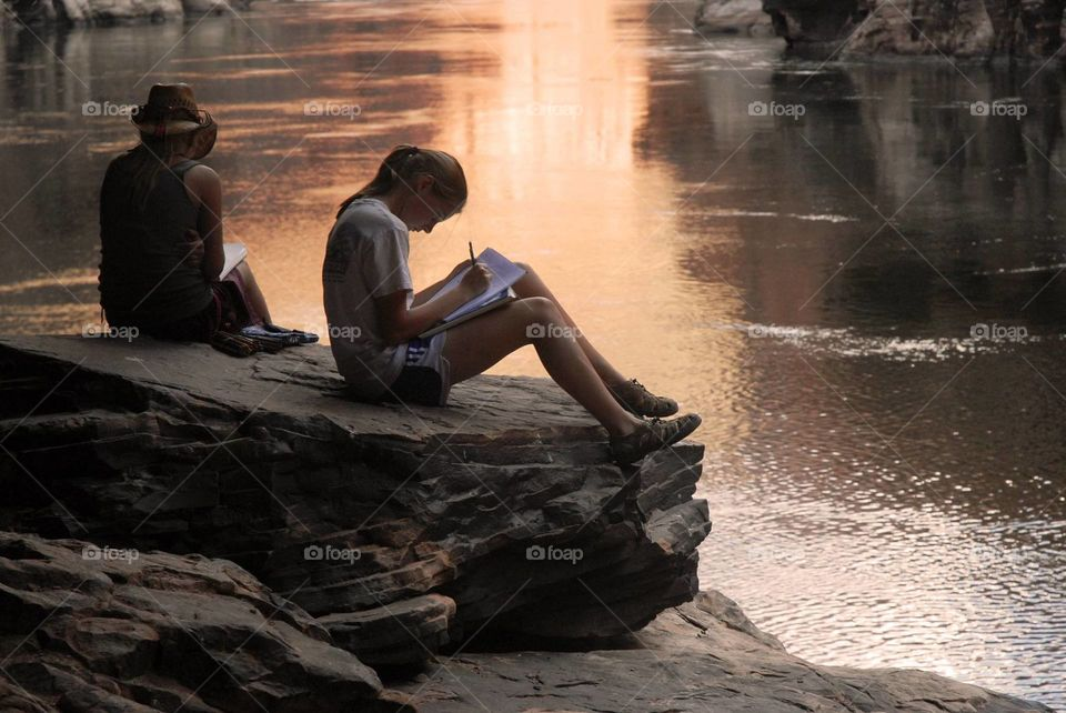 Teenage girls sitting on rock studying near lake