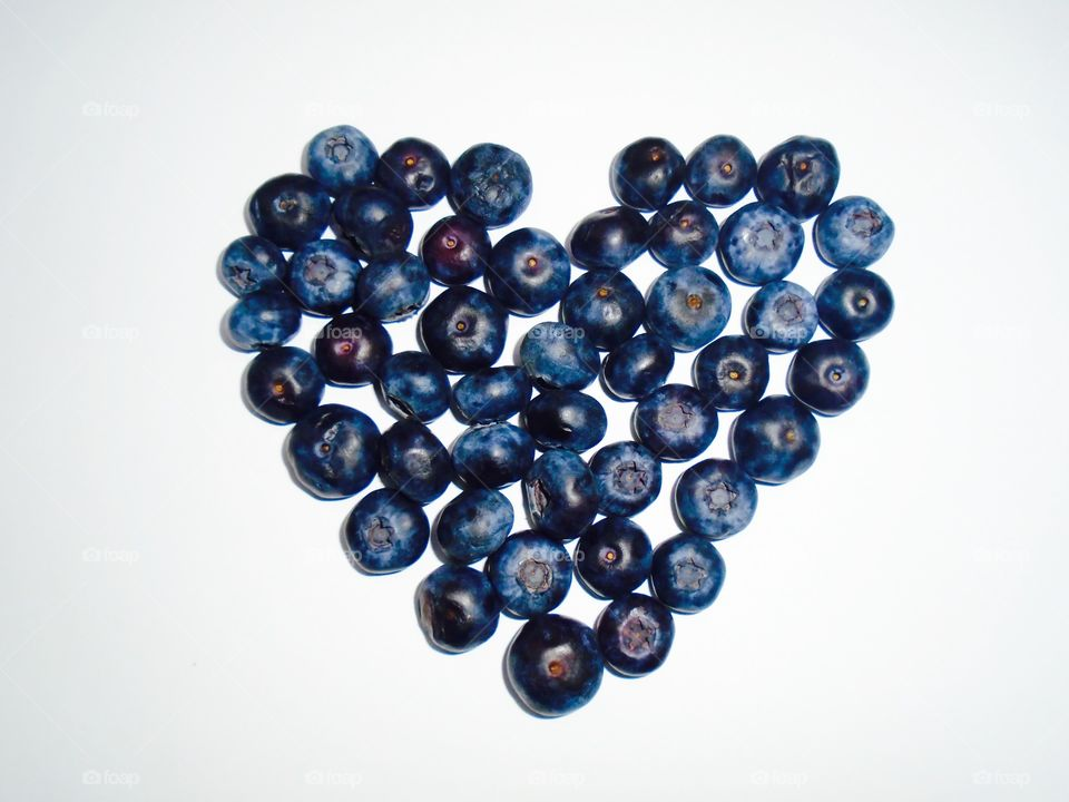 Heart made from blueberries on white background