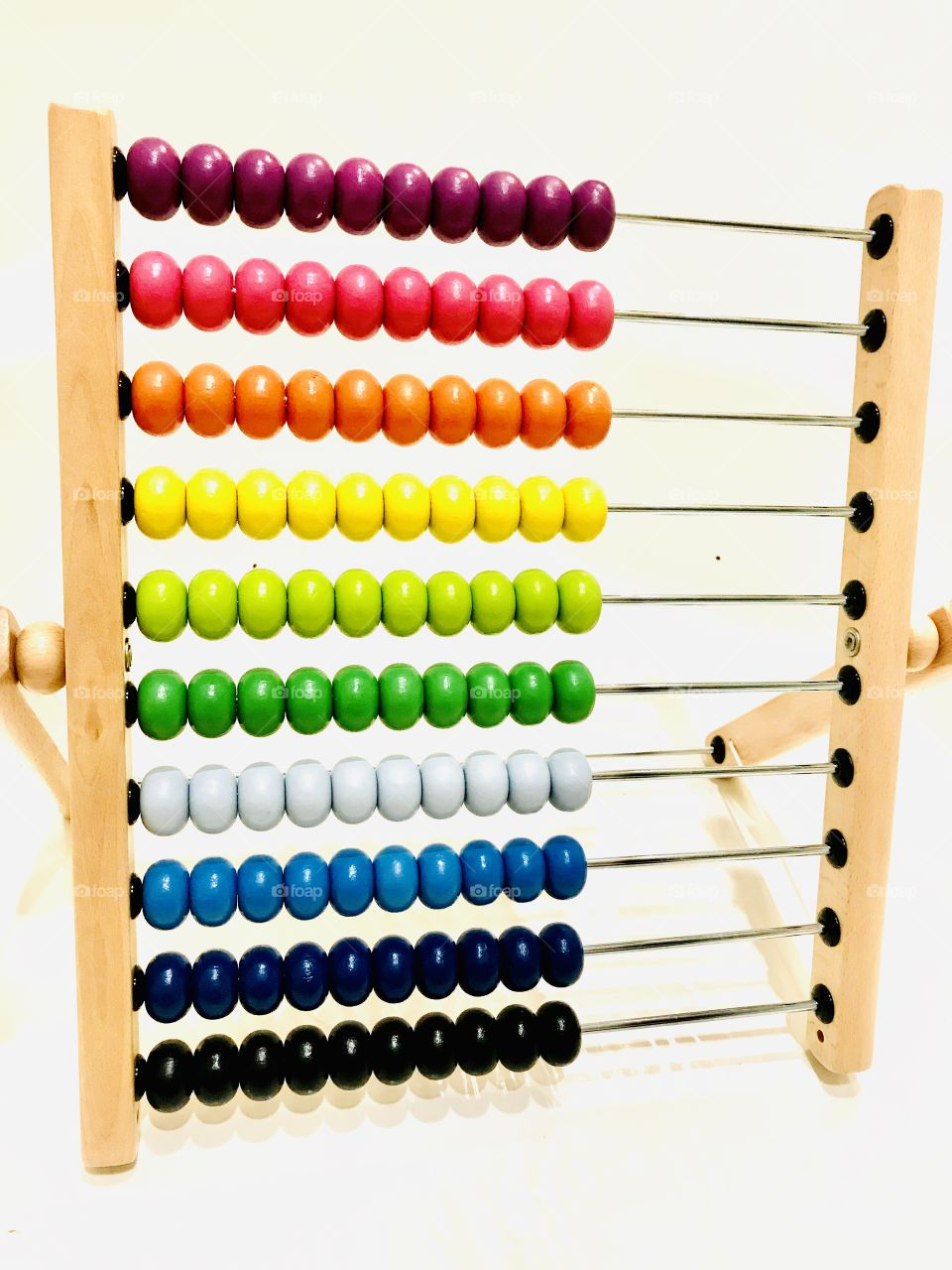Gorgeous very colorful photo of rainbow colored abacus beads displayed against white background.