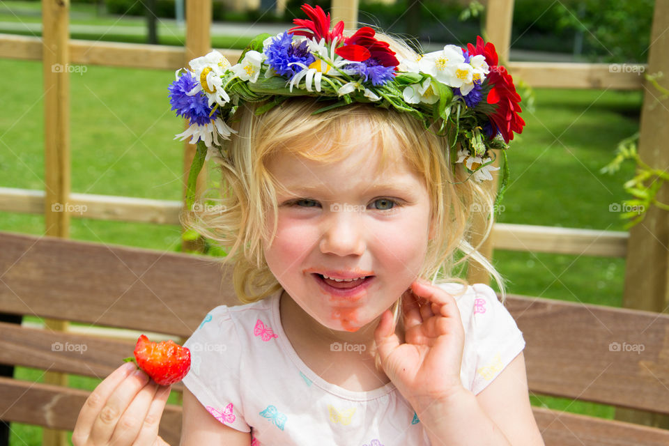Portrait of a girl with crown eating strawberry