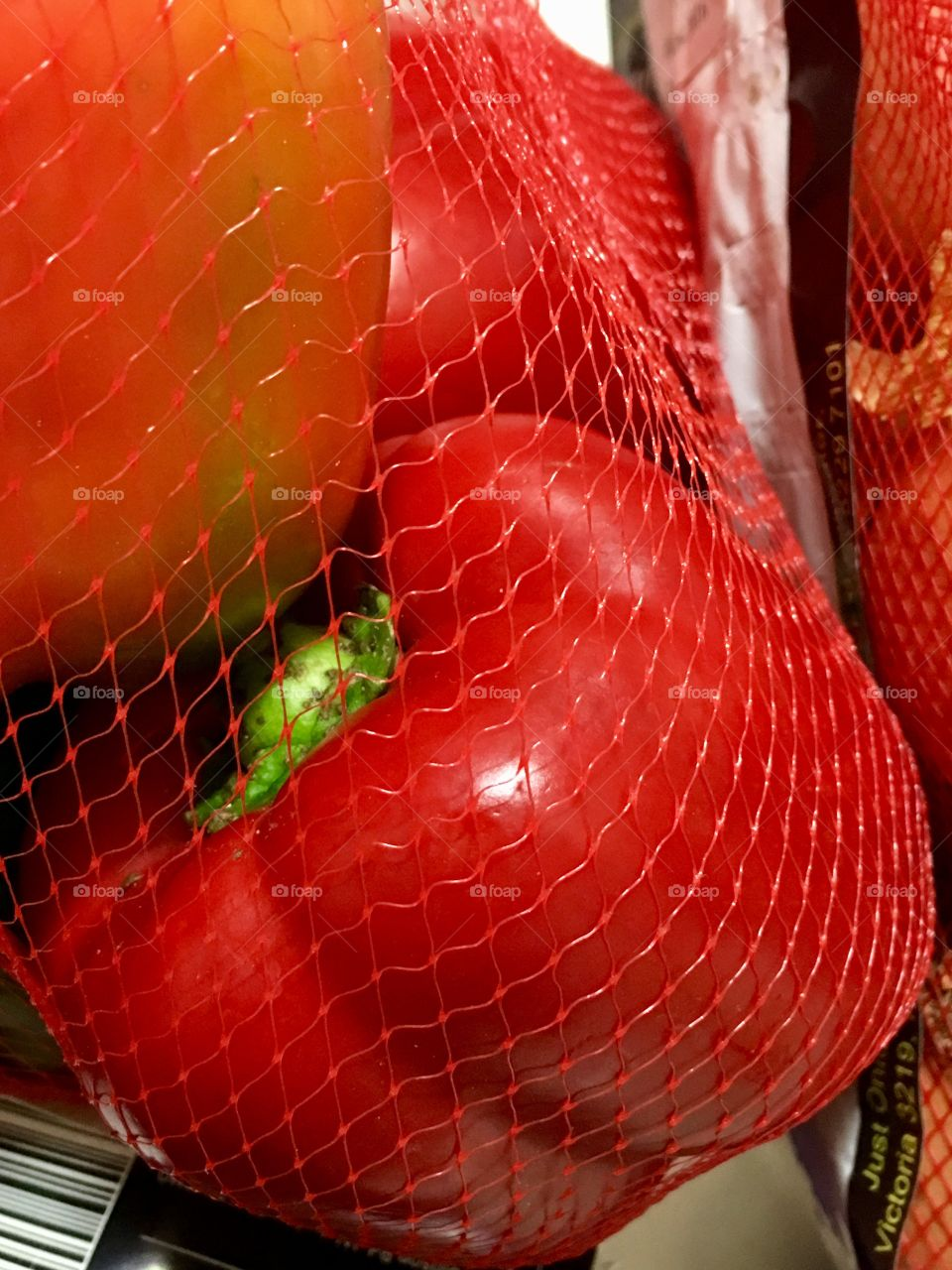 Red sweet bell pepper capsicum in red plastic mesh
