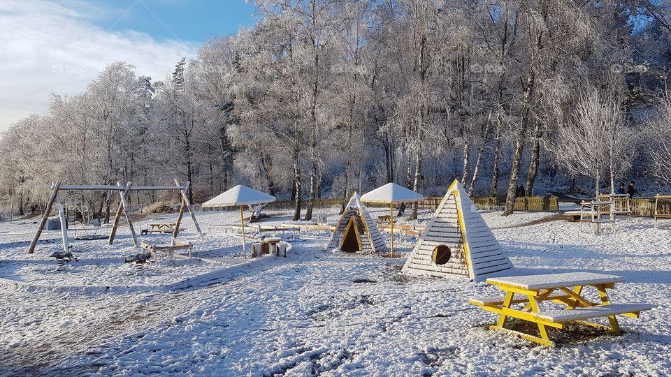 Children's playground in beautiful winter landscape in snow - lekplats i vackert vinterlandskap