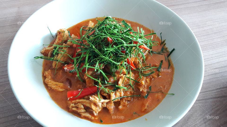 Thai chicken curry in bowl on table