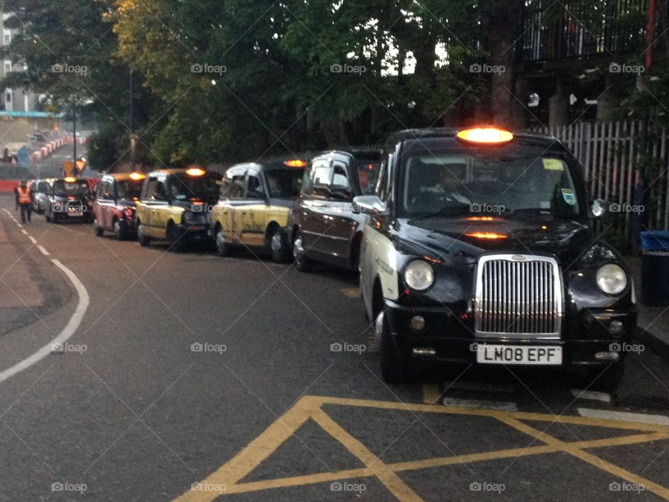 Row of empty black London cabs taxi