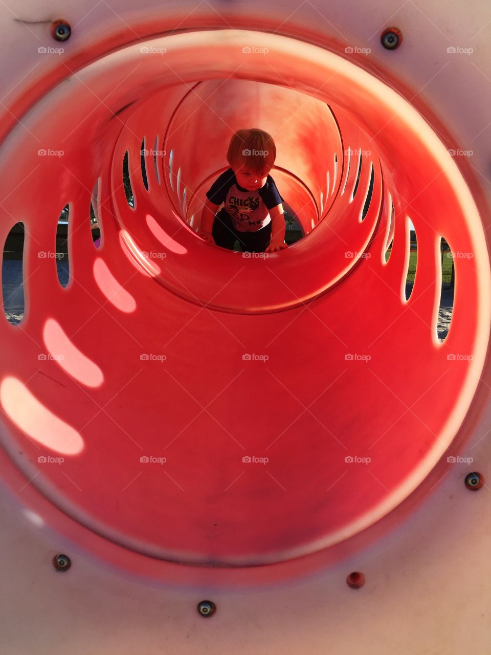 Baby crawling inside the red tunnel