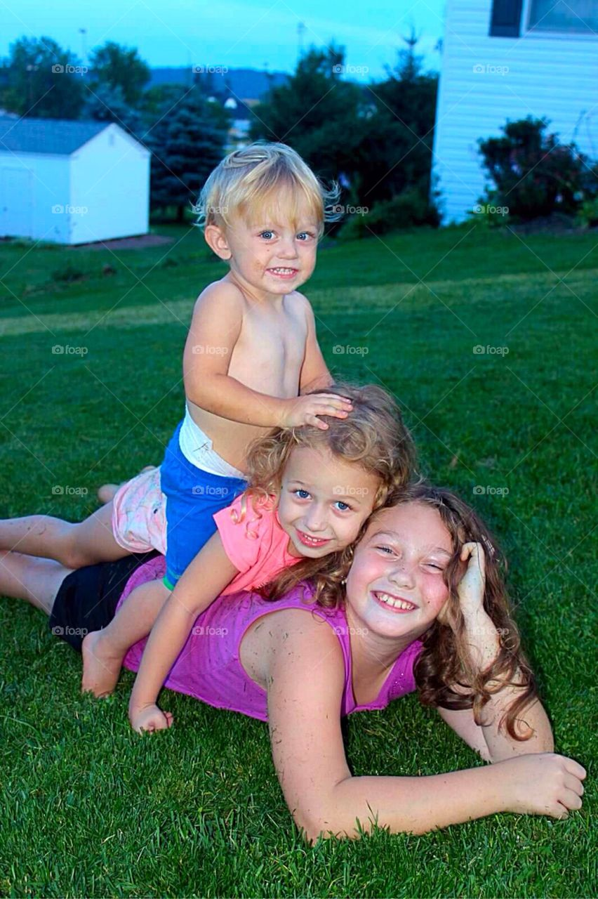 Brother and sisters playing on grass in a heap