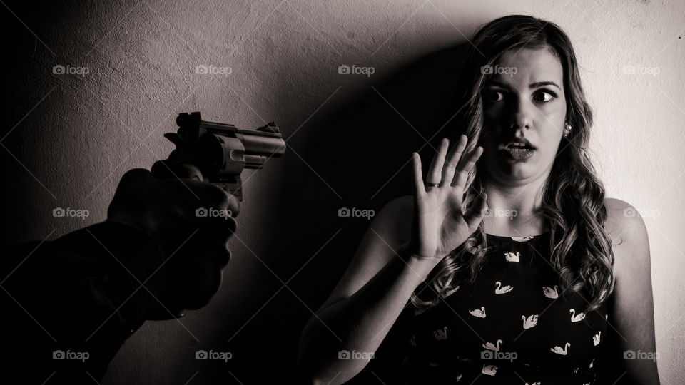 A person threatening woman with gun