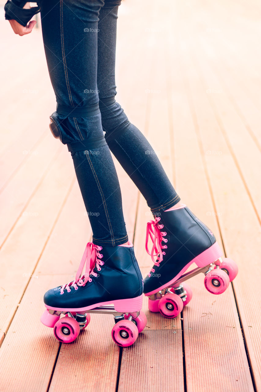 Close-up of female legs in roller blades on wood