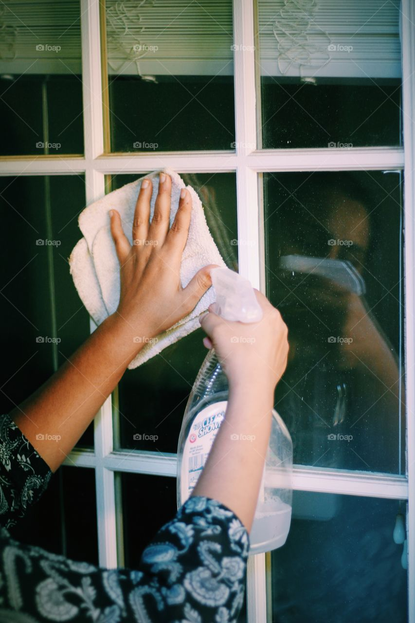 Young woman doing home cleaning. Daily chores and housework cleaning the glasses on door