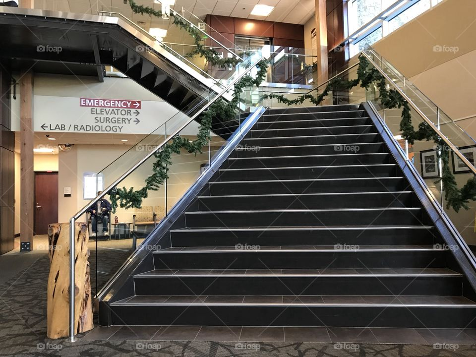 A two level stairway decorated with garland for the holiday season leads to an upper floor of a building.