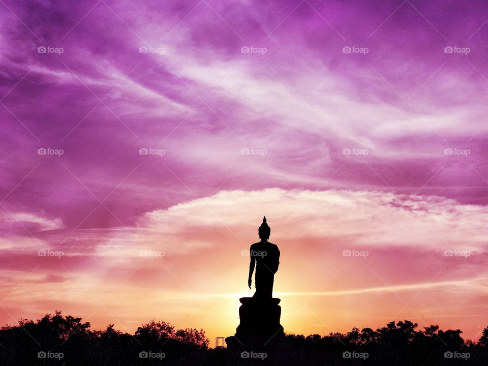 Buddha image in walking posture during sunset at Buddhamonthon, Nakhon Pathom, Thailand