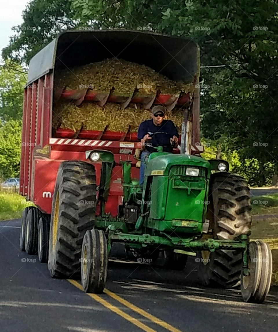 Young Farmer Driving John Deere Tractor with Trailer Full of Silage