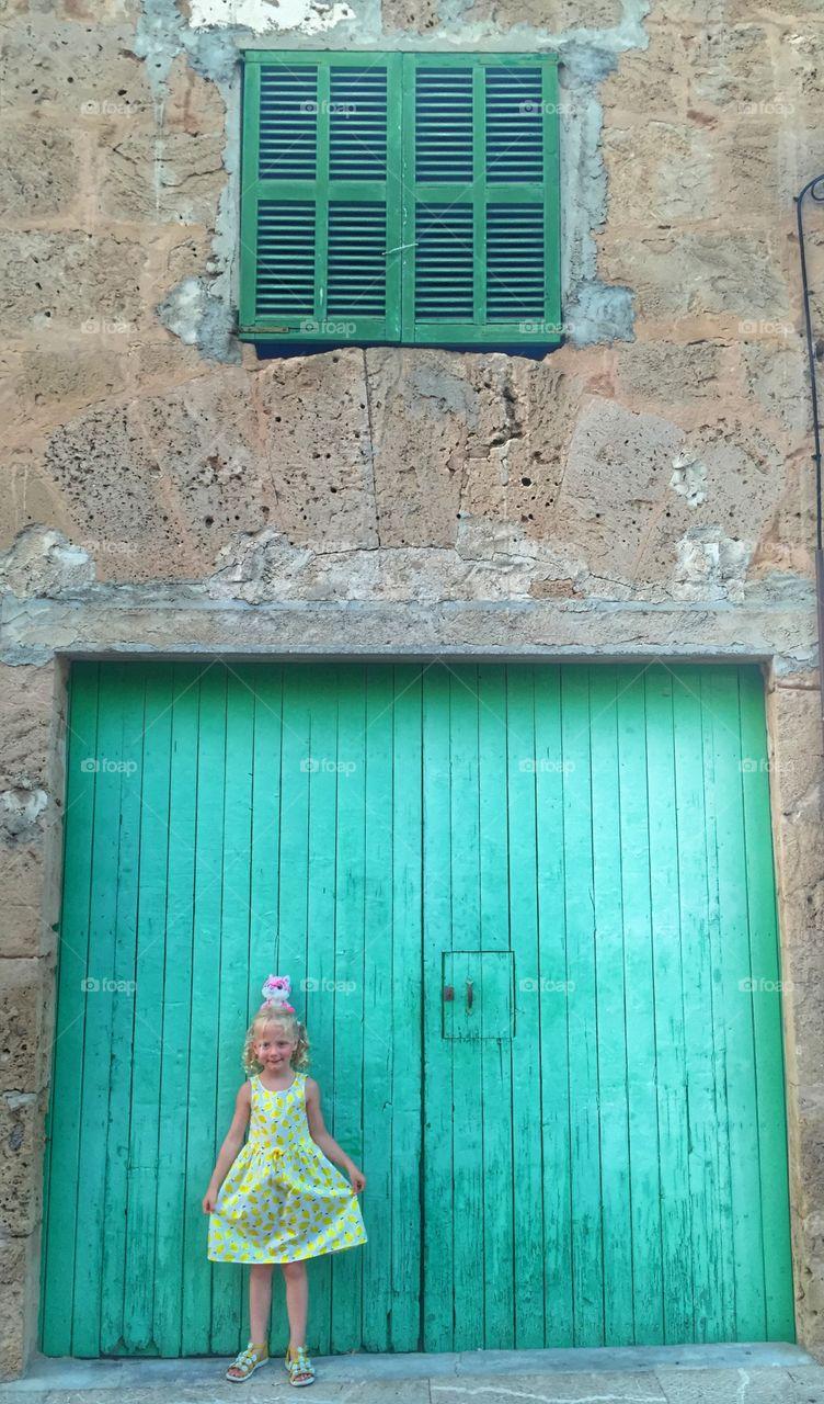 Portrait of a girl standing on closed door