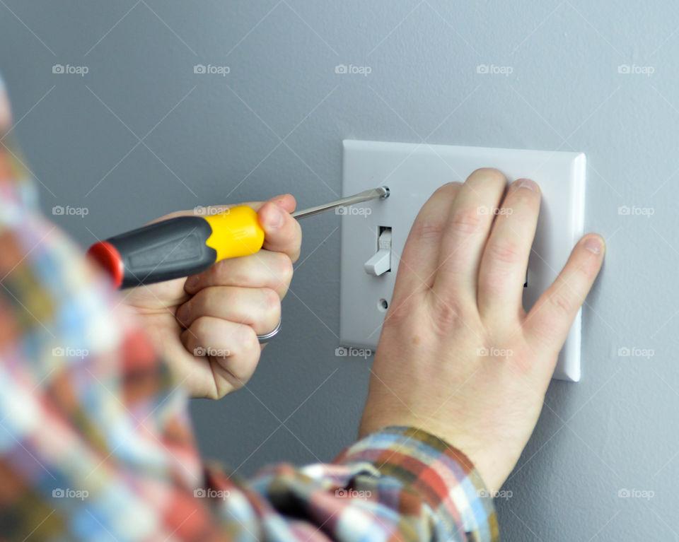Handyman screwing on a light switch plate