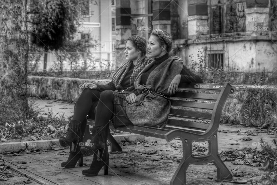 Two young woman sitting on bench