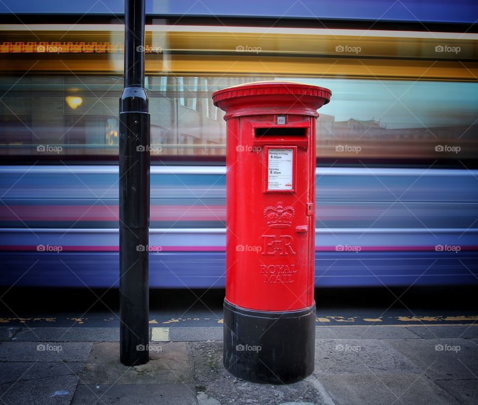 A bright red Royal Mail post box on the city streets with a motion blurred bus in the background creating a colourful abstract image.