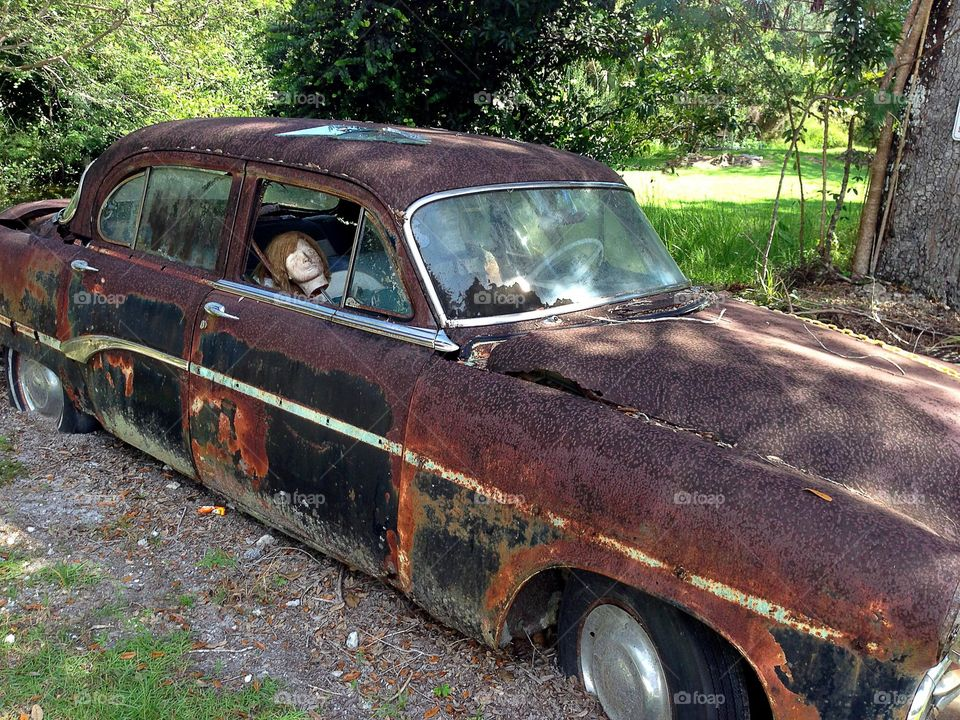 Rusty wrecked car with head inside, perfect imperfection