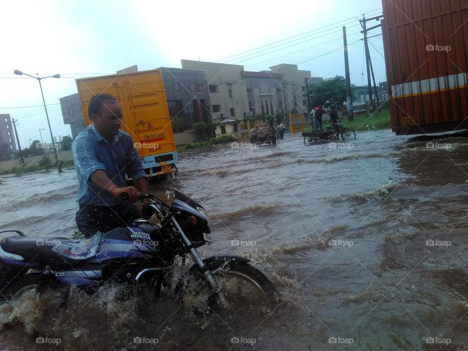 Man with motor bike in flood