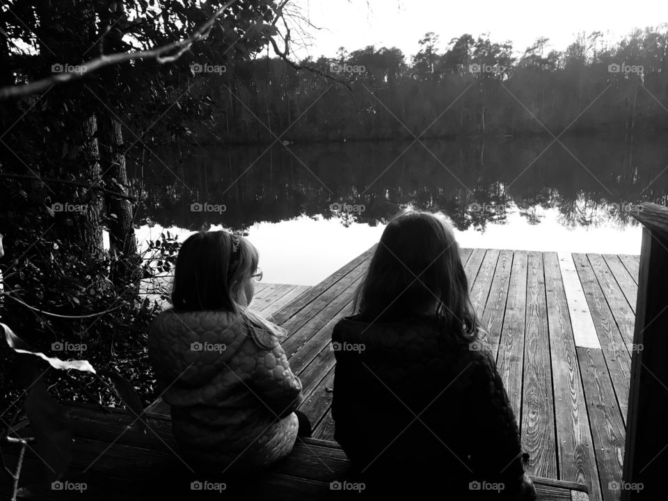 Sisters bonding at the dock of the pond at sunset