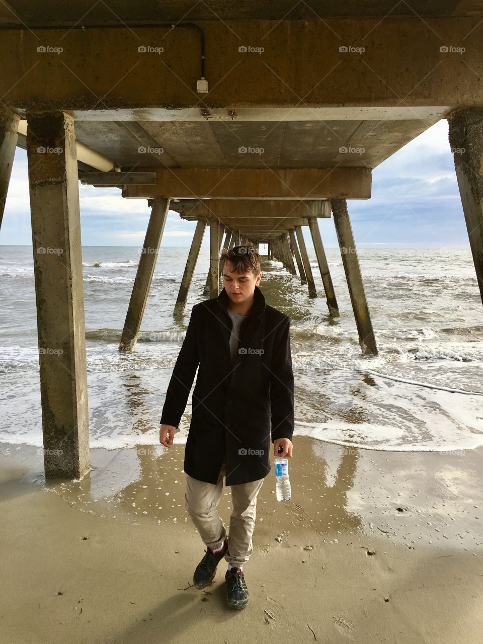 Stylish young man wearing black wool coat and holding water bottle walking toward camera under ocean Jetty