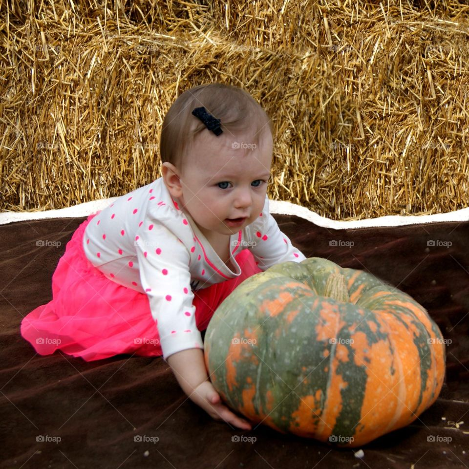 Close-up of a baby girl with pumpkin