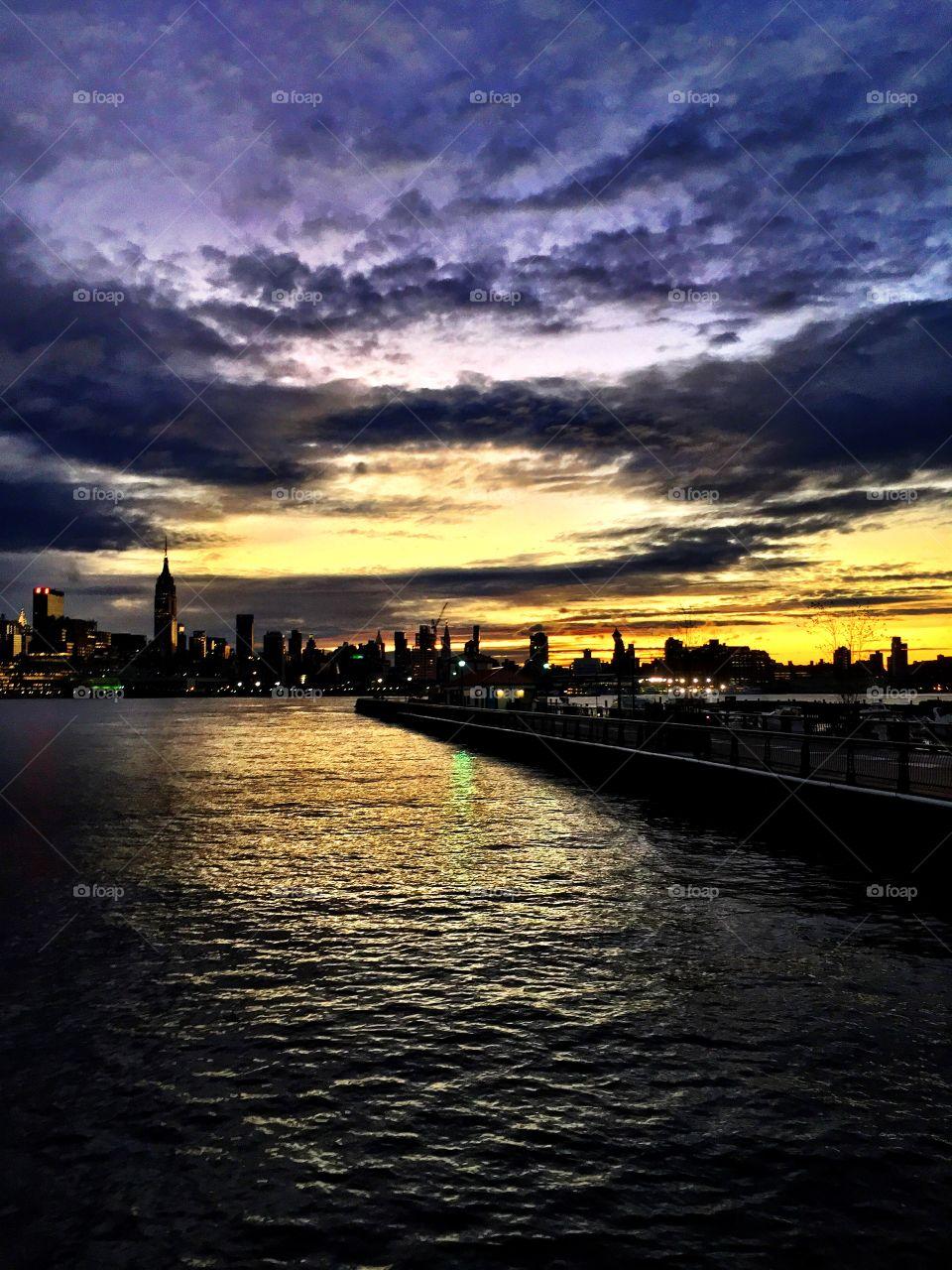 New York City skyline at sunrise with purple skies.. New York City skyline at sunrise with purple skies. Hudson River view,
