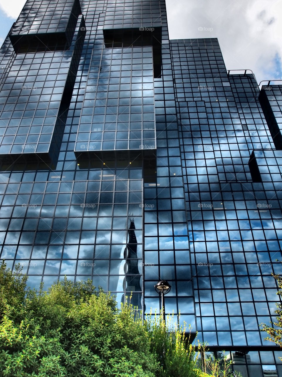 Amazing modules on a glass building reflecting the clouds in the sky in London exhibiting creative modern architecture.