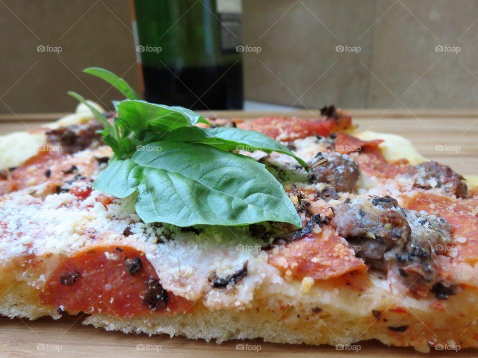 Basil, cheese, sausage, pepperoni and mushroom pizza.