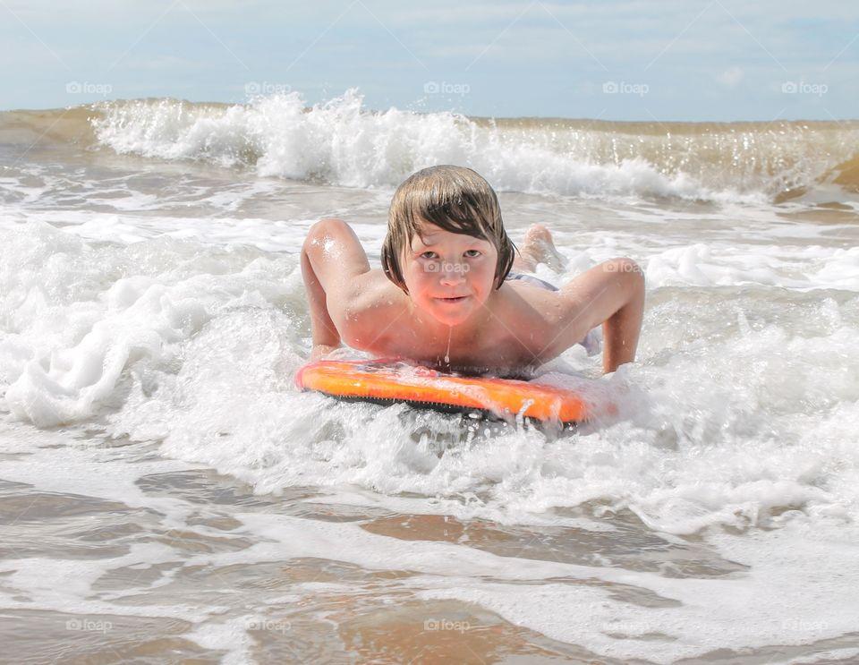 Small boy enjoying on surfboard
