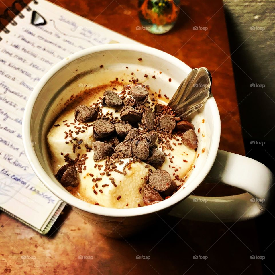 Hot cocoa with marshmallows and chocolate chips/sprinkles. Journal in the background.