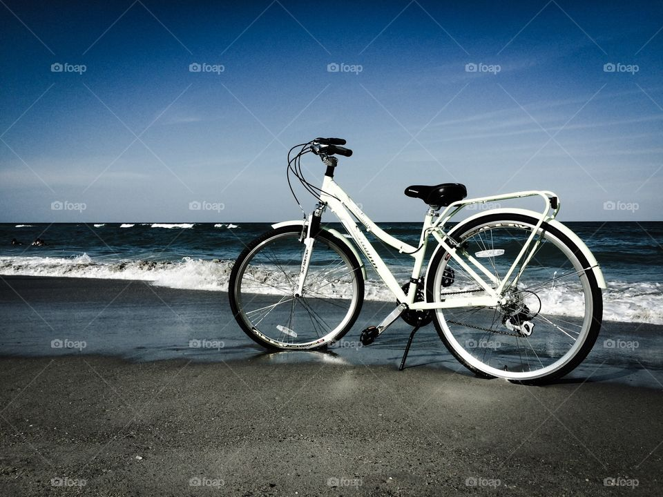 Bike at Beach. The surf rolls in and the bike takes in the view after a long ride in the wet sand.