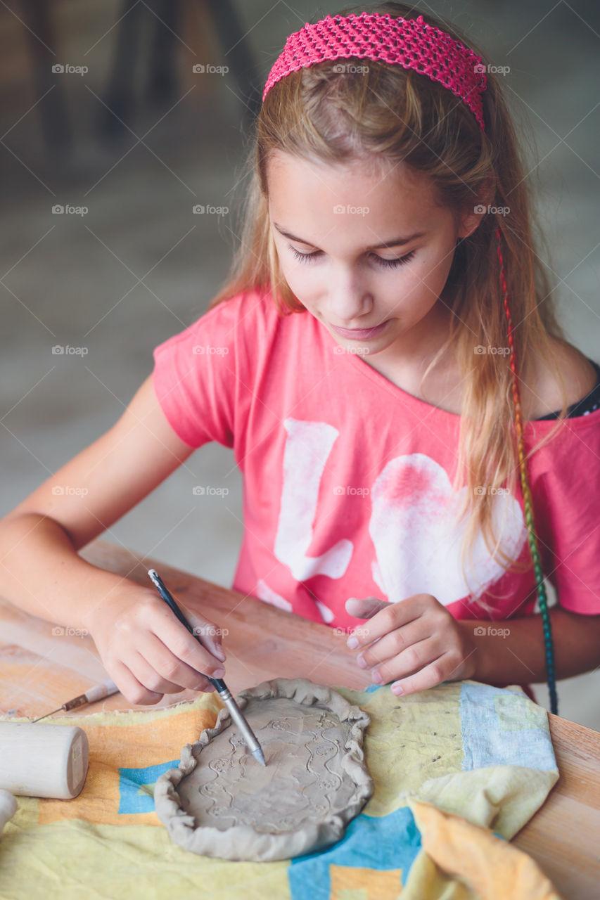 Girl making design on mud clay