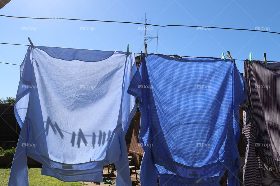 Two shirts hung up to dry on clothesline's on sunny day, shadows of clothes pegs clothespins on shirts