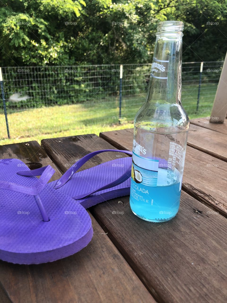 A cool blue drink on deck along with purple flip flops.
