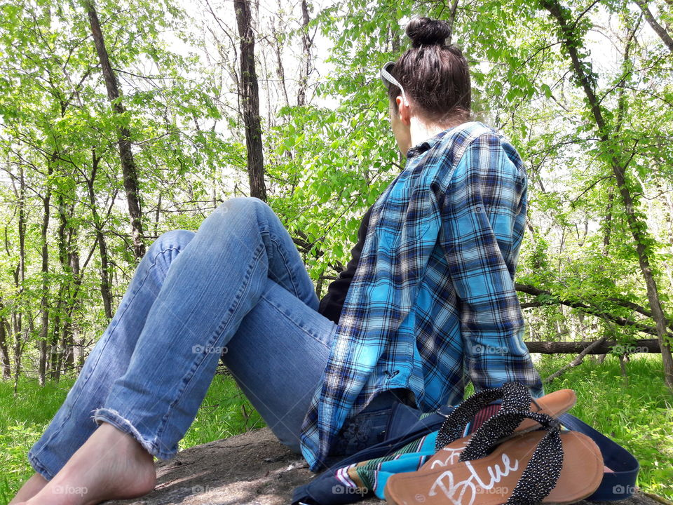 Woman sitting in the forest looking trees