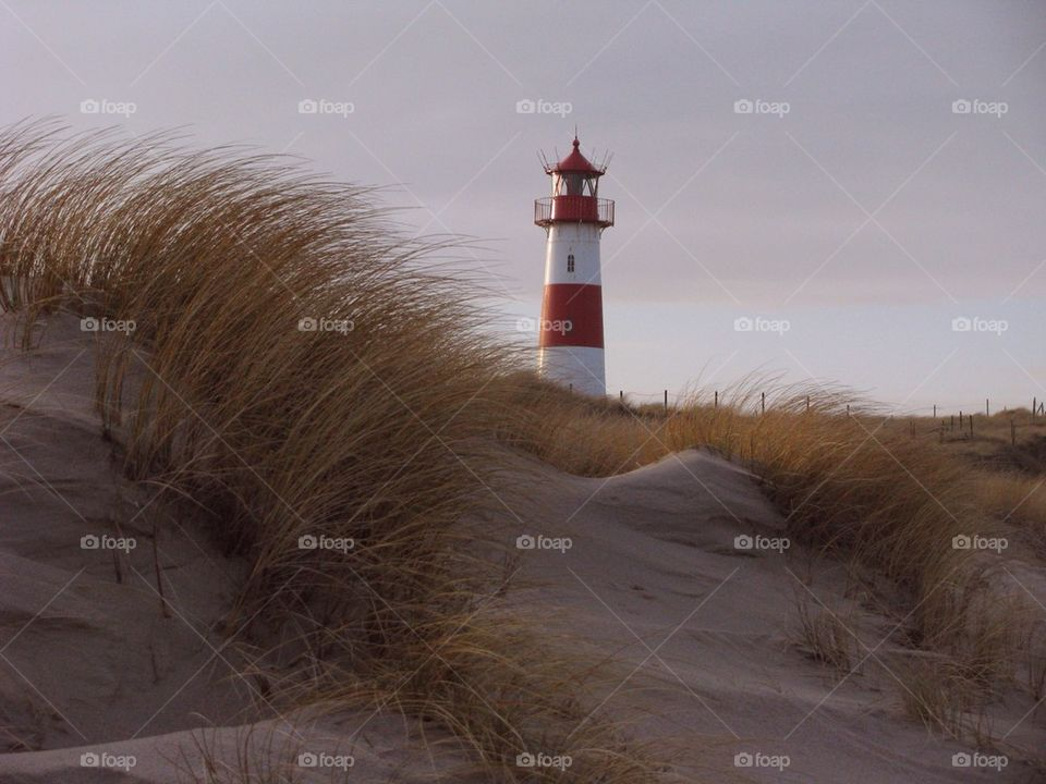 Red and white lighthouse at sea