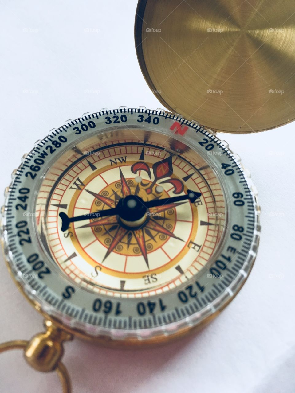 Gold and black compass facing North East direction.