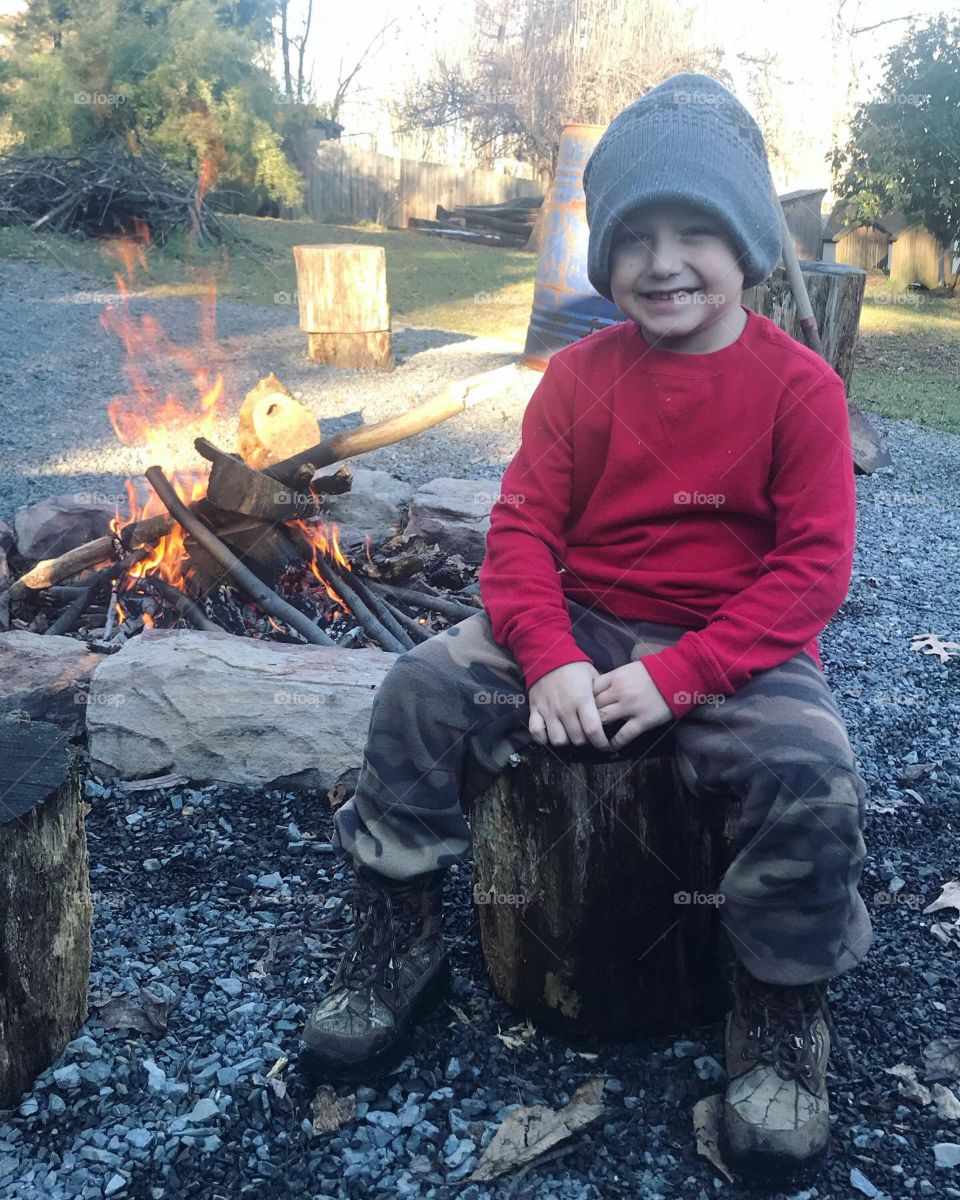 My adorably handsome little son keeping himself warm by the campfire on a crisp day outside.