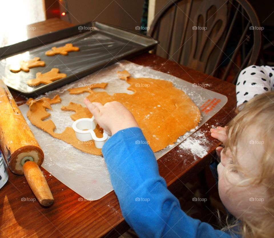 Child making gingerbread men for Santa.