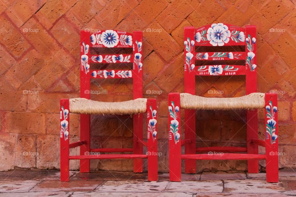 Two colorful red handcrafted straw chairs spotted on the sidewalk in San Miguel de Allende, Mexico,