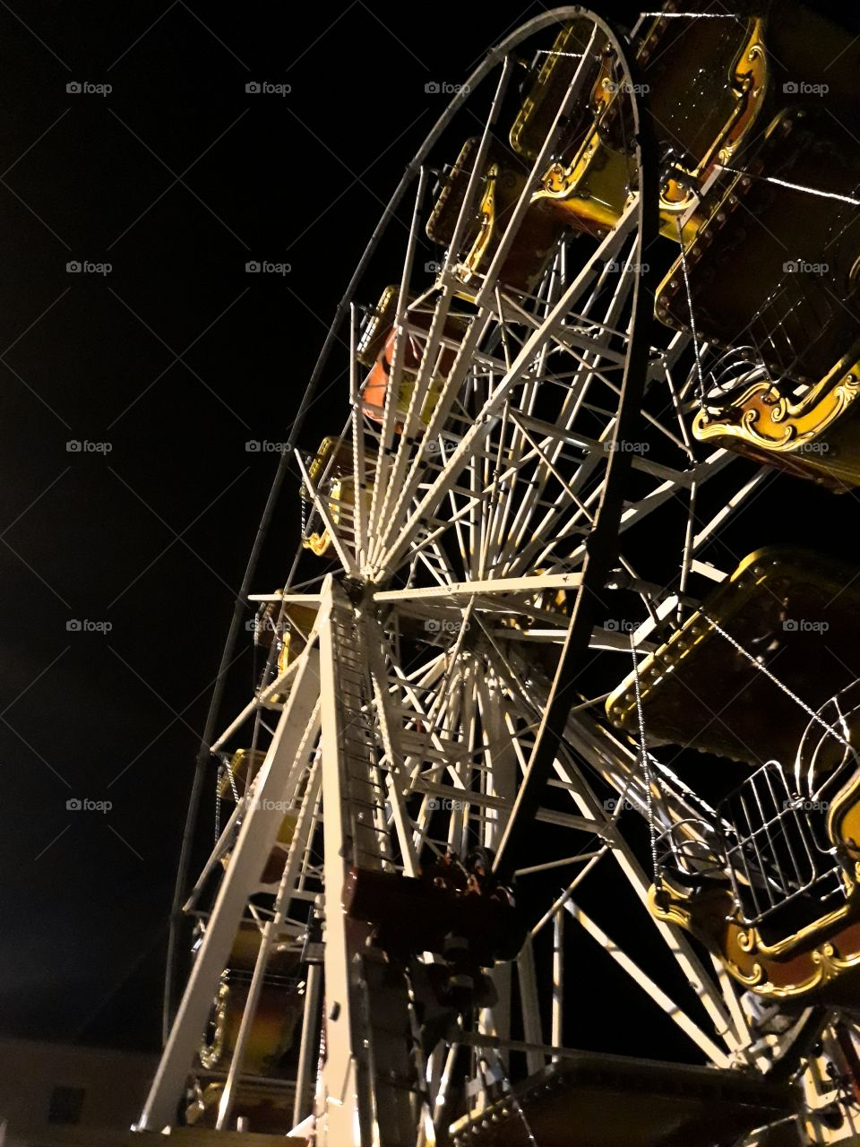 A little metal ferris  wheel photographed from below at night with a clear sky. The colours and the Shape of the Wheels recalls childhood Memories