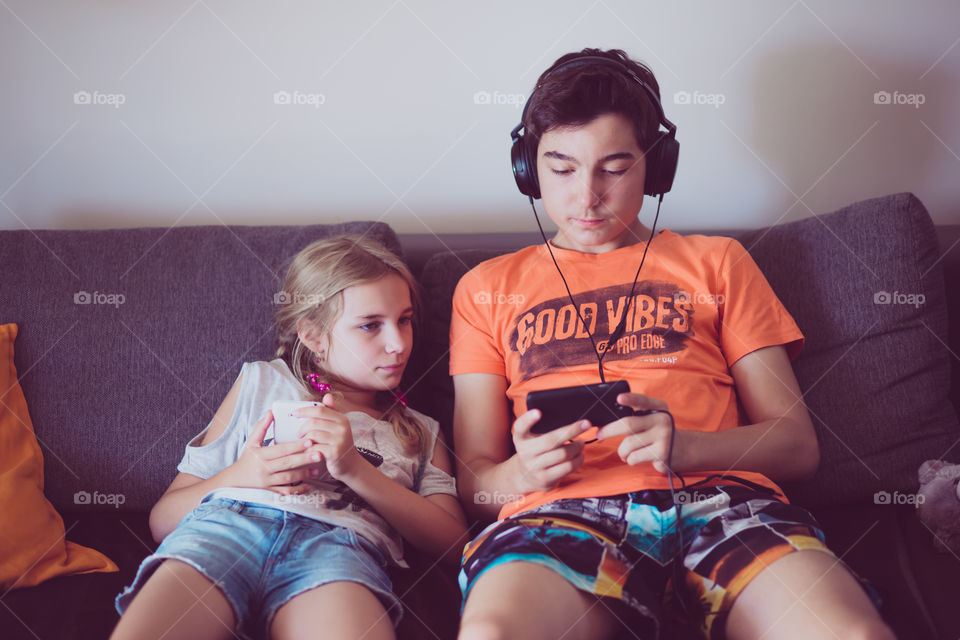 Brother and sister watching video in smartphone