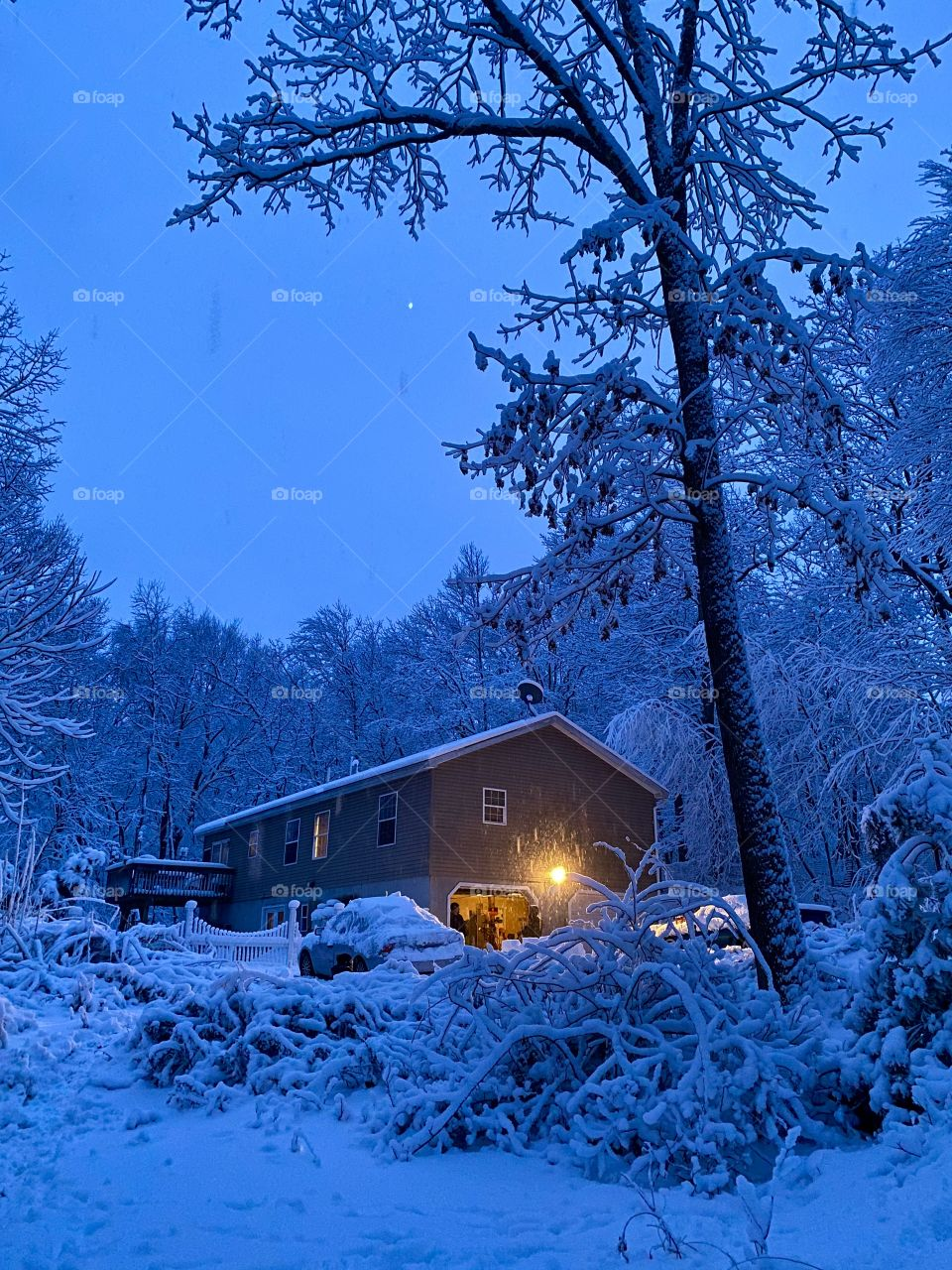 Night during a snow storm in Northeast Pennsylvania USA; A house surrounded by snow covered woods and an open sky with the garage light on.