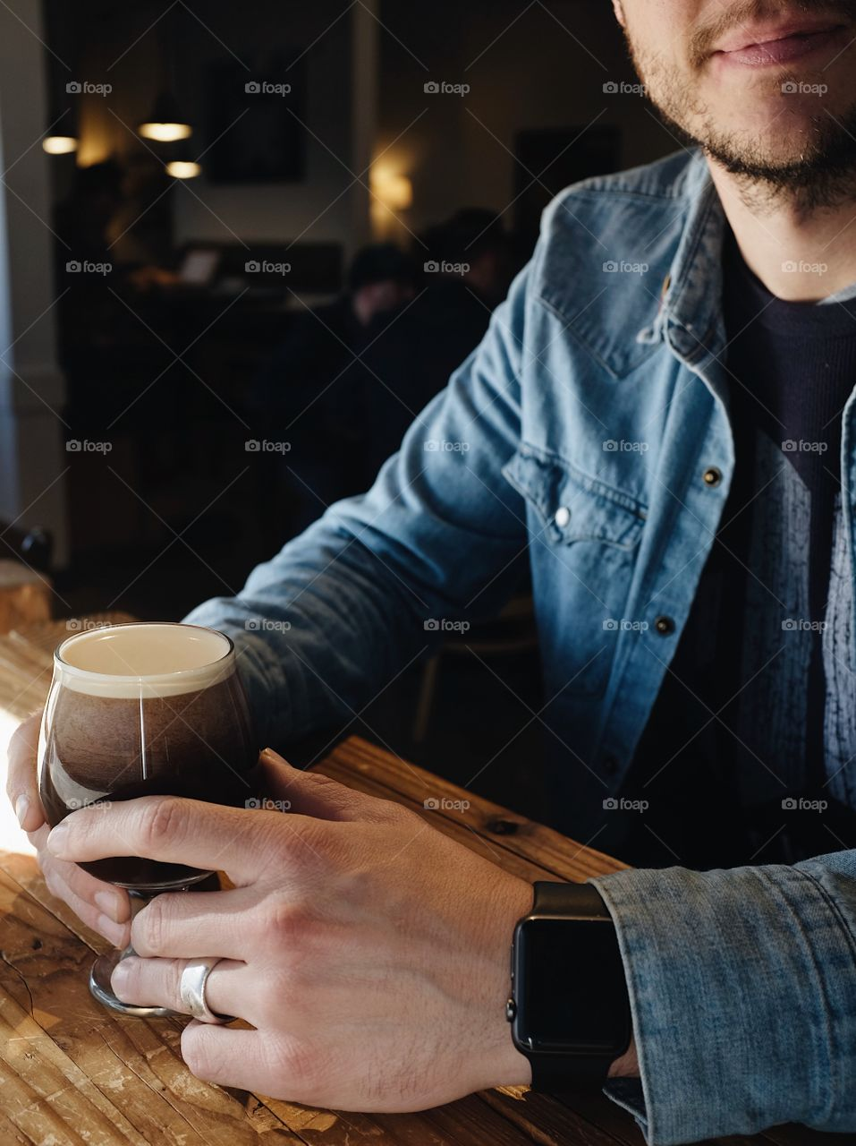 A married man sitting in a window enjoying a nitro cold brew coffee. He is wearing an Apple Watch, a Jean jacket, and a wedding ring on his finger.