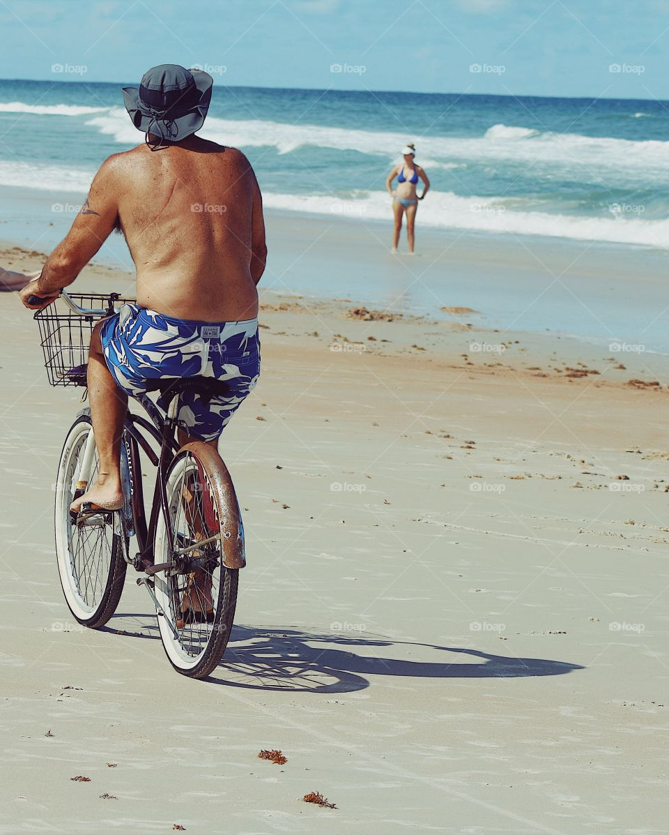 Beach lover cycling in summer