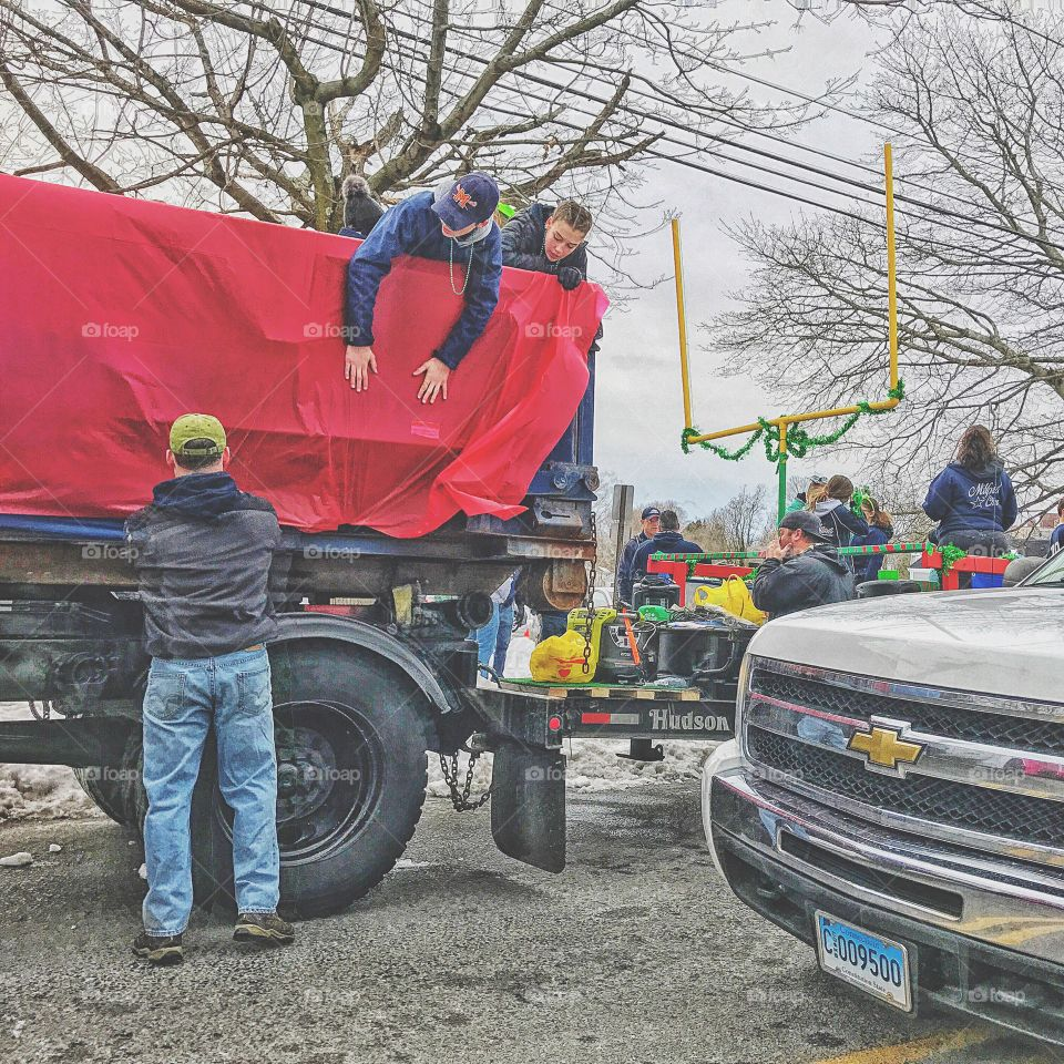 Group of people placing sheet on truck