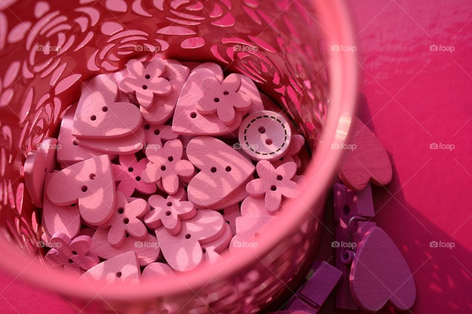 pink color wooden buttons and wood hearts  pink background