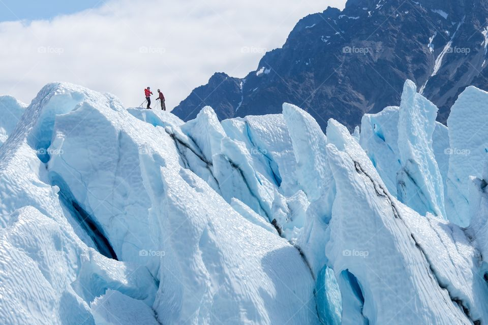 Two climbers top of glacier. Two climbers reached the top of iceberg. Challenging and hostile environment. Matanuska glacier, Alaska, USA