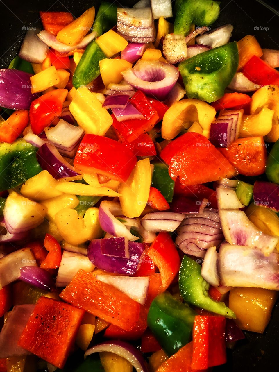 Clash of colors chopped and cooking red yellow green bell peppers and purple onion meal prep