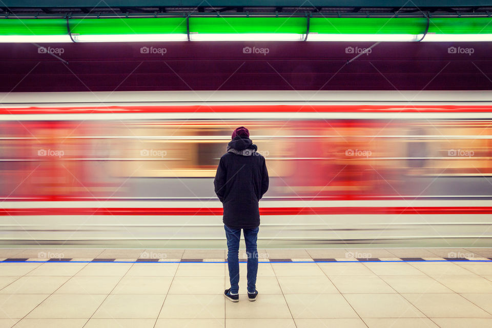 Man standing in front of moving train on platform